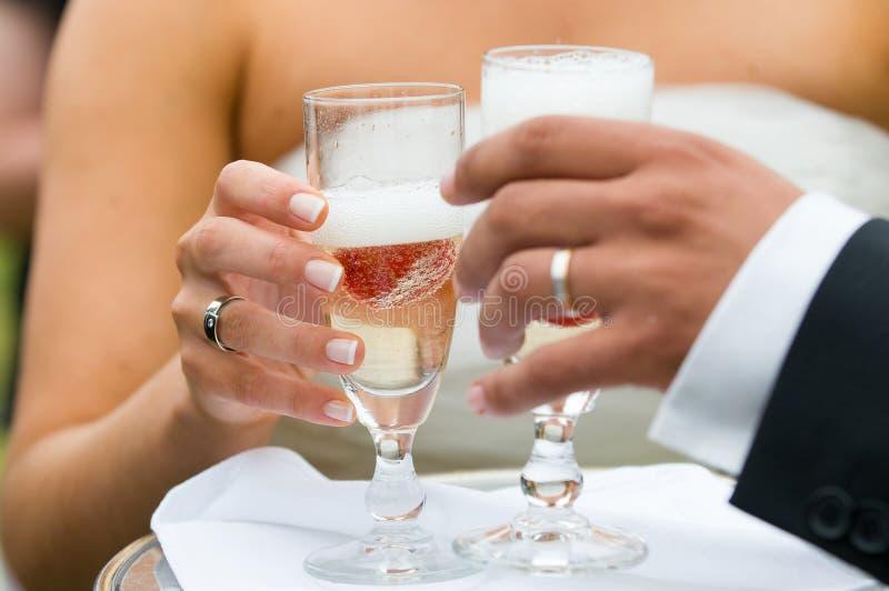 Zwei Hände, die einen Champagner Glas halten stockfotografie