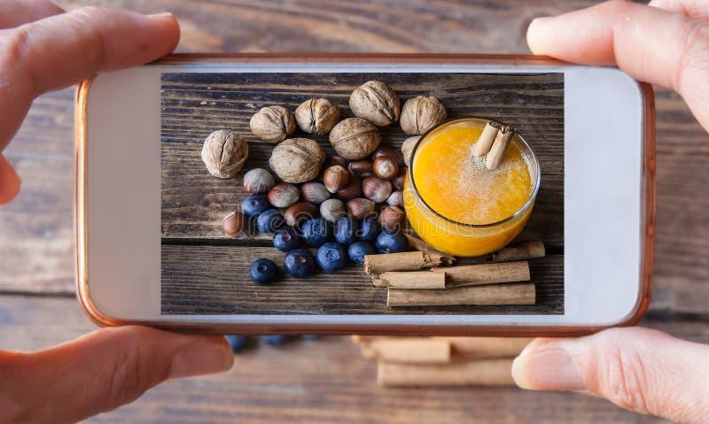 Zwei Hände, die einen Handy macht ein Foto des Herbstlebensmittels halten lizenzfreies stockfoto