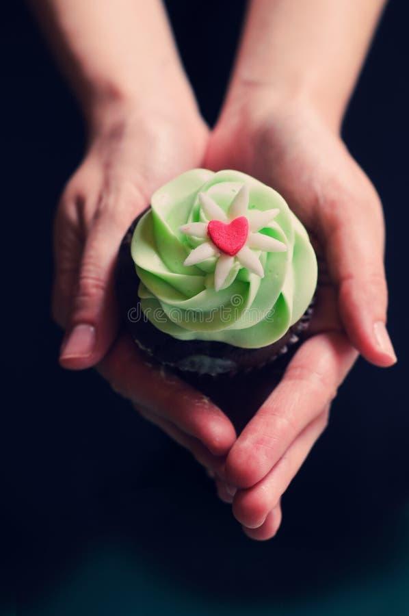 Zwei Hände, die kleinen Kuchen anhalten lizenzfreie stockbilder