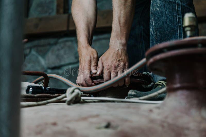 Zwei Hände halten ringsum Flansch auf Metallbau stockfotos