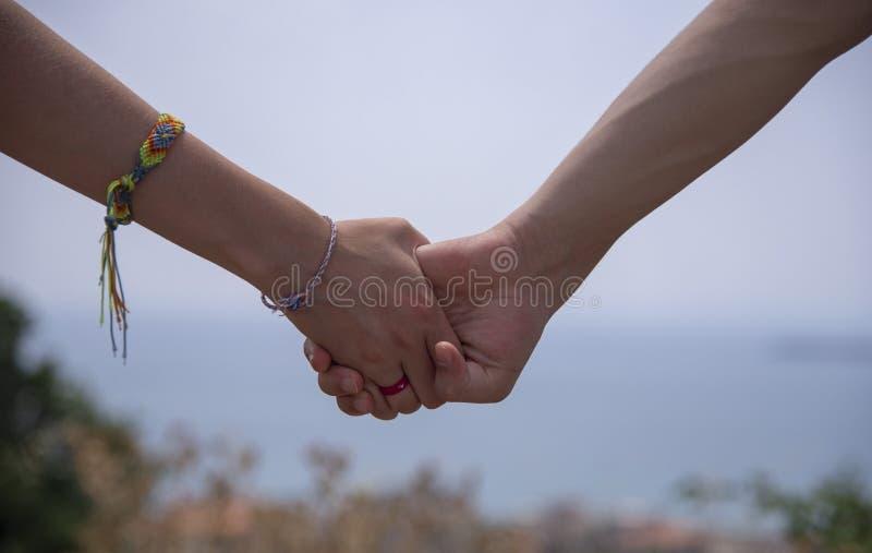 Zwei Hände, Mann und Frau, auf einem unscharfen hellen Hintergrund fest halten Auf der weiblichen Hand ist ein helles Armband stockbild