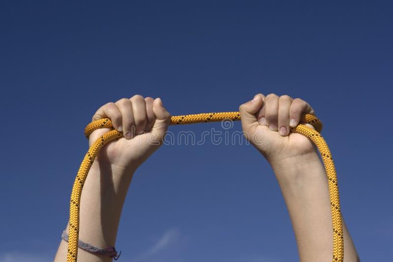 Zwei Hände mit einem orange Seil lizenzfreie stockbilder