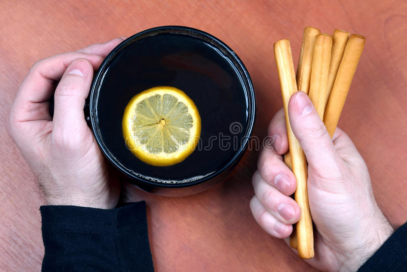 Zwei Hände mit einer Tasse Tee und Kekse schließen oben stockbilder