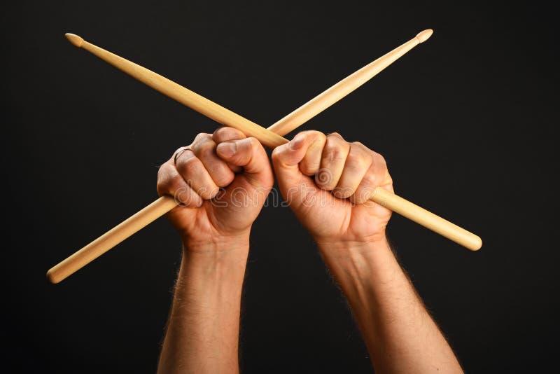Zwei Hände mit gekreuzten Trommelstöcken über Schwarzem lizenzfreie stockfotos