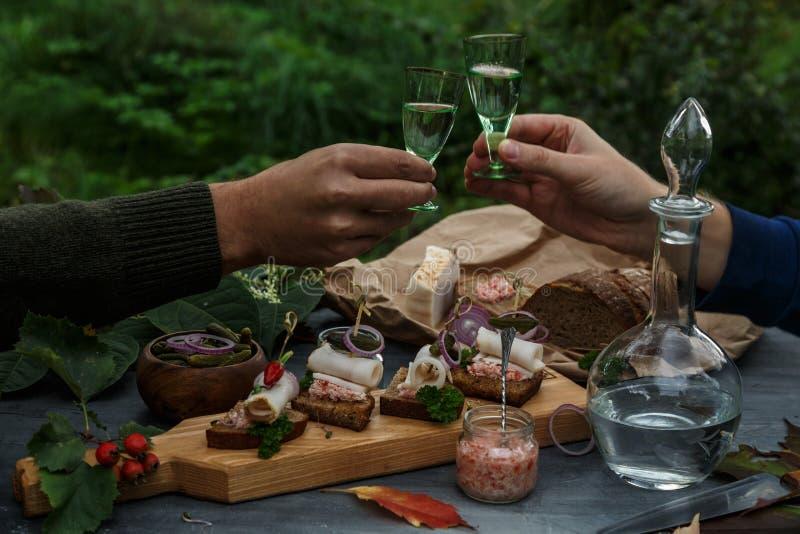 Zwei Hände mit Schüssen des Wodkas, äußeres Abendessen stockbilder