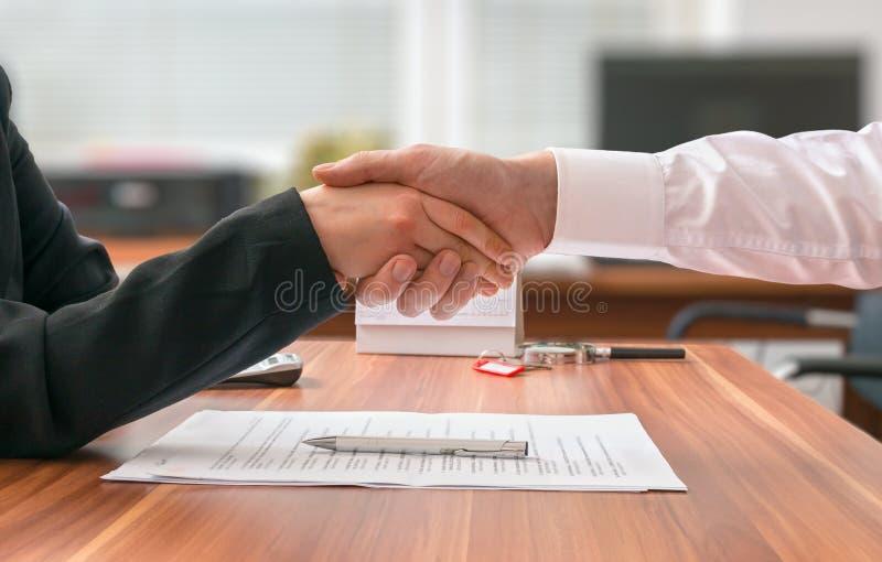 zwei Hände mit verschiedenen Stücken des Puzzlespiels Geschäftsmann und Frau, die hinter Schreibtisch mit Vereinbarung sitzen lizenzfreies stockbild