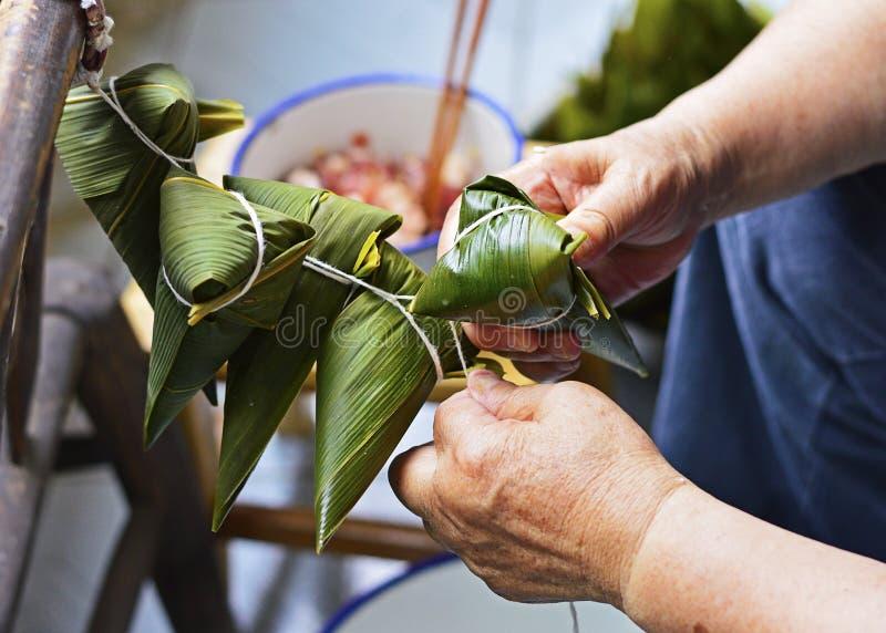 Zwei Hände ziehen die Schnur über dem Blatt fest, um Zongzi, traditioneller Chinese-Reis-Mehlklöße zu machen für Dragon Boat Fest stockbild