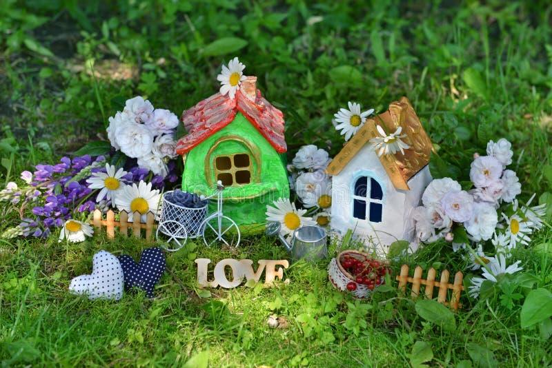 Zwei Häuser mit Dekorationen, Liebesbriefen, Blumen und Beeren lizenzfreies stockbild