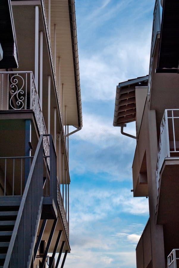Zwei Häuser stehen nebeneinander, Balkone, Treppe, Dächer, gegen den blauen Himmel stockbilder