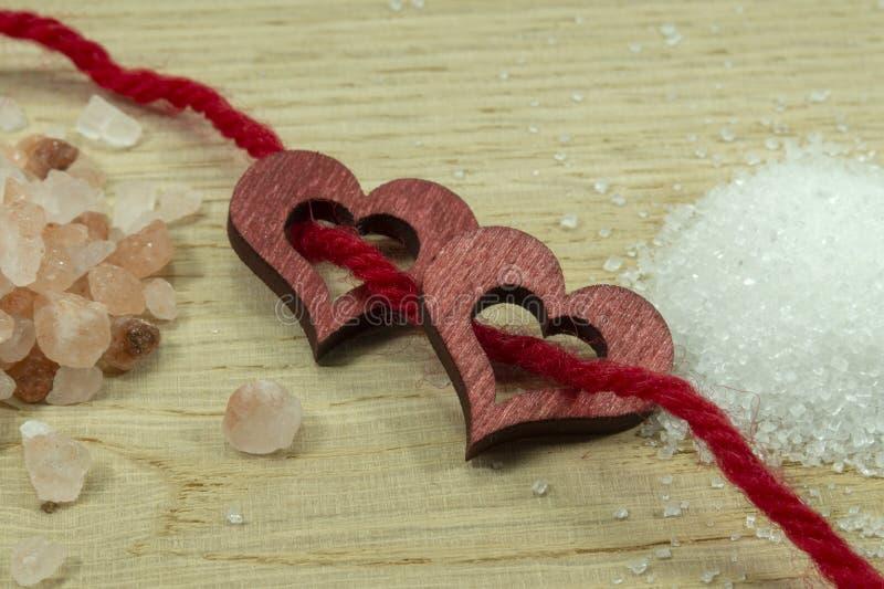Zwei hölzerne dekorative Herzen verlegt auf rotem Seil stockbild