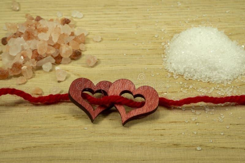 Zwei hölzerne dekorative Herzen verlegt auf rotem Seil lizenzfreie stockfotografie