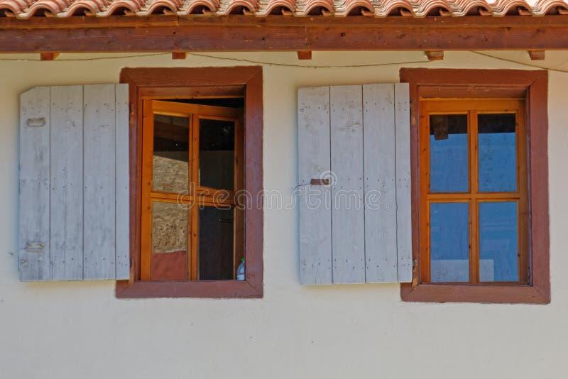 Zwei hölzerne Fenster der Weinlese auf blasser weißer Wand lizenzfreie stockfotografie