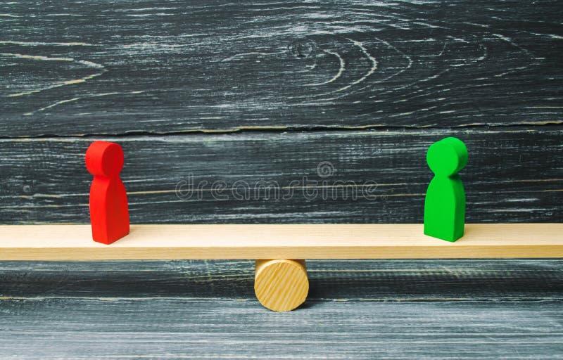 Zwei hölzerne Zahlen stehen auf den Skalen von Gerechtigkeit rivalen Geschäftskonzept des beiderseitigen Nutzens und Erfolg von T lizenzfreie stockfotos