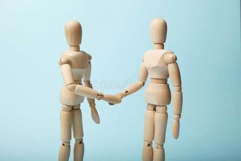 Zwei hölzerne Zahlen von Mannerschütterungshänden stockbilder