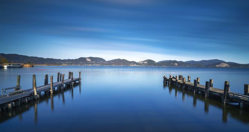 Zwei hölzerner Pier oder Anlegestelle und auf einer blauen Seesonnenuntergang- und -himmelreflexion auf Wasser Versilia Toskana,  stockfoto