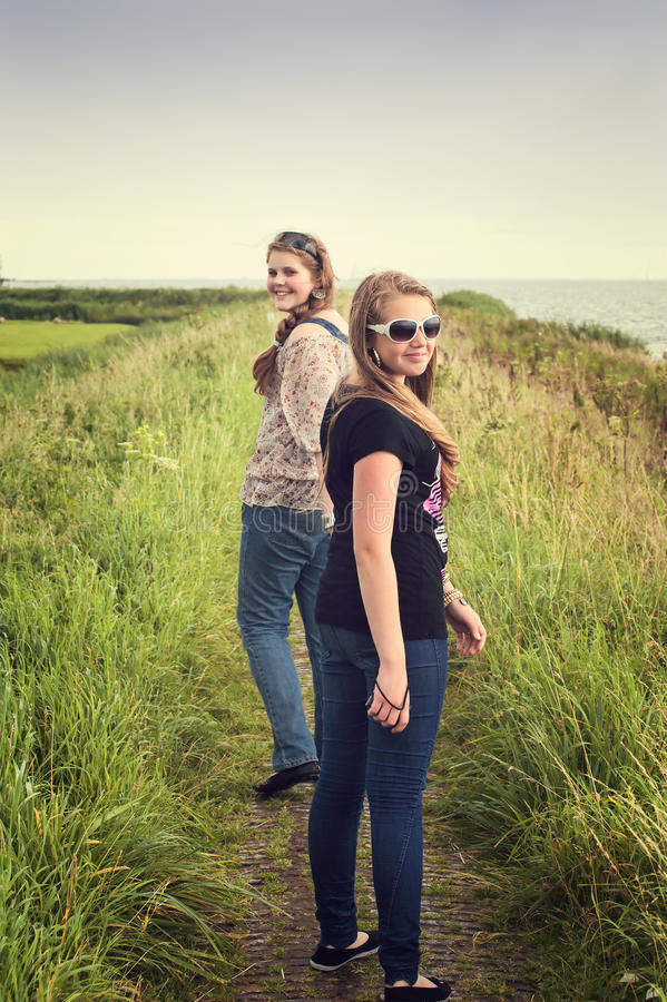 Zwei hübsche Jugendliche, die auf einen Dike gehen lizenzfreies stockbild