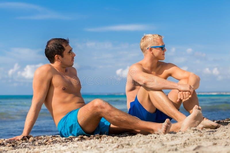 Zwei hübsche junge Männer, die auf einem Strand plaudern lizenzfreie stockfotografie