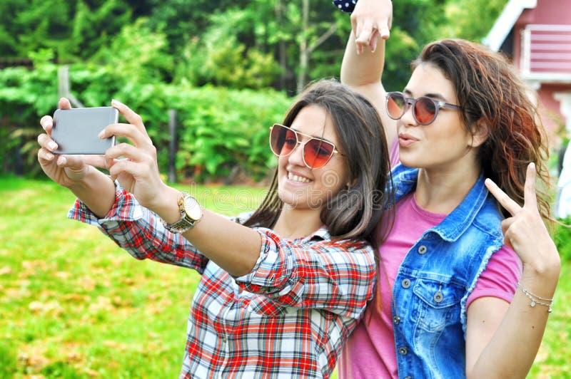 Zwei hübsche Mädchen des frohen Fanny, die den Spaß nimmt ein selfie auf Mobile haben stockbild