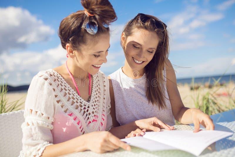 Zwei hübsche Mädchen, die am Cafétisch auf Strandlesemenü sitzen stockbilder