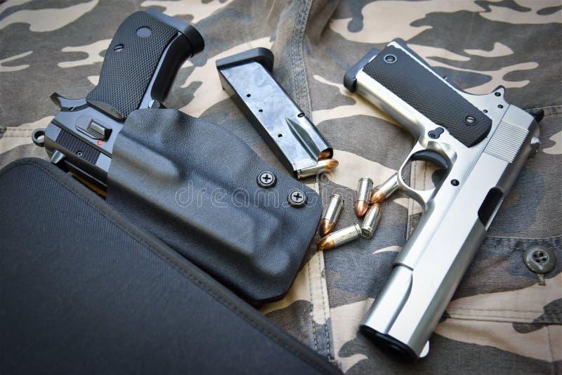 Zwei halbautomatische Pistolen auf Tarnungssoldathose stockfoto