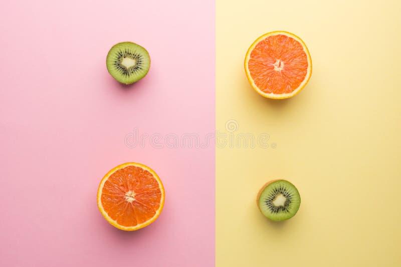 Zwei halbe Orange und halbe Kiwi zwei auf Geometrie-Gelb-Rosa-Pastellhintergrund, Draufsicht lizenzfreie stockfotos