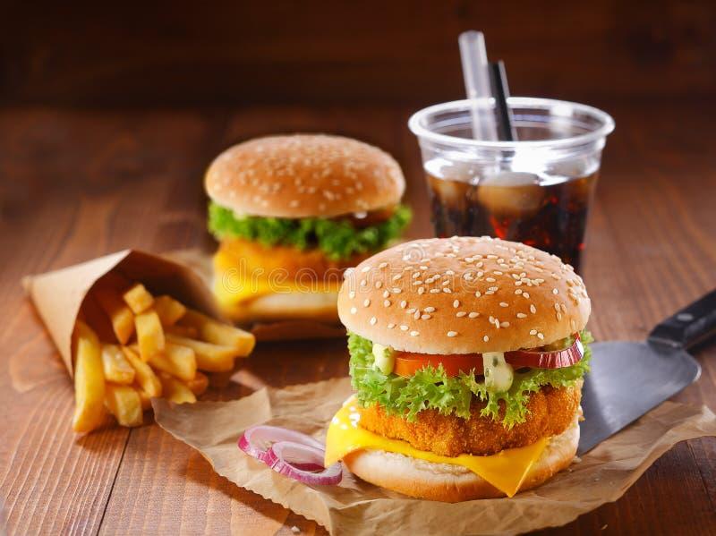 Zwei Hamburger, gebratene Kartoffeln und Soda stockfotos