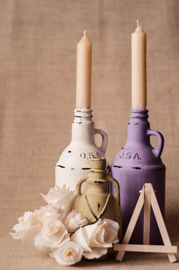 Zwei handgemachte Kerzen der Pitcher, farbige Lampen, Papierrosen, weißes Gestell lizenzfreie stockbilder