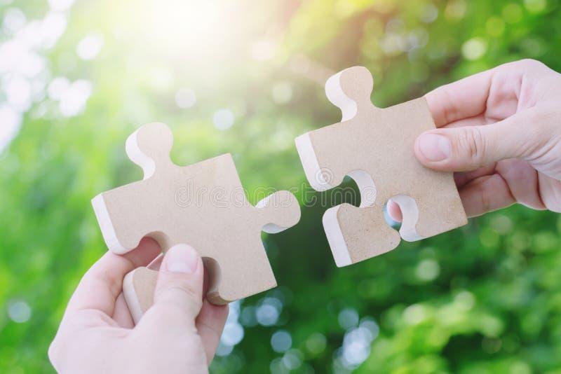 Zwei Handperson, die versucht, Puzzlespielstück der Paare mit neuem Hintergrund des Baums anzuschließen zackiges hölzernes ein Te stockbild