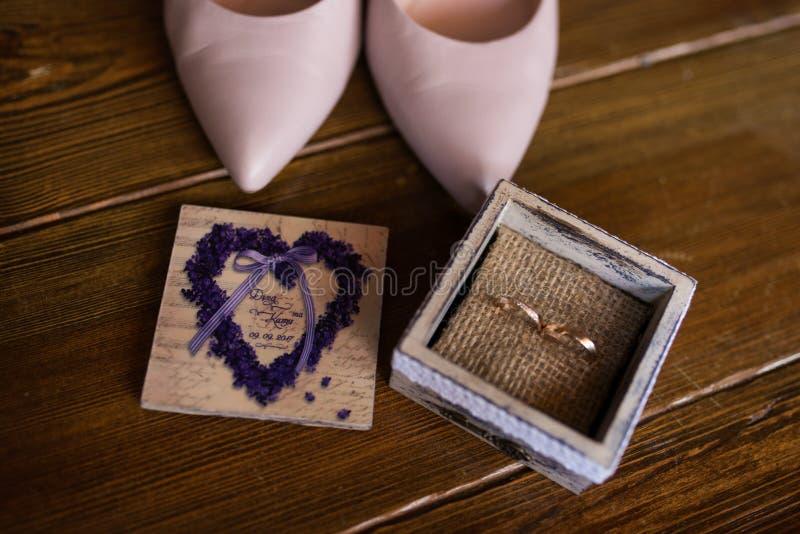 Zwei heiratende goldene Ringe in der Holzkiste Nahe der Stellung von bräutlichen rosa Schuhen lizenzfreies stockfoto