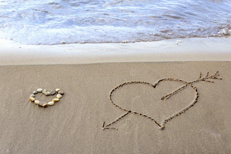 Zwei Herzen auf Sand eines Strandes stockbilder