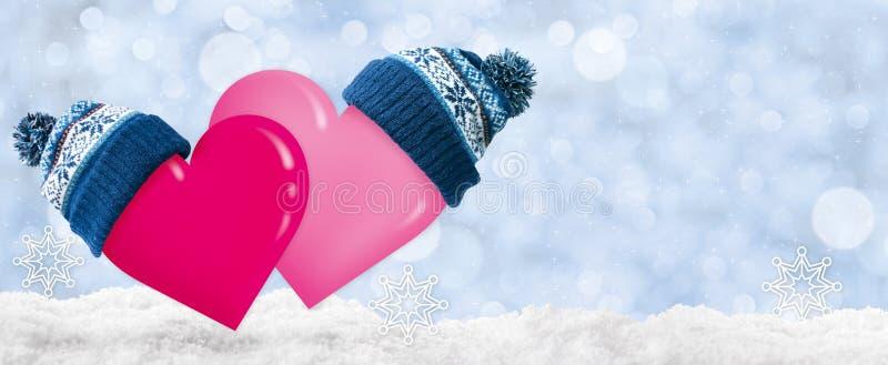 Zwei Herzen in den Kappen mit Pompoms für Valentinstag stockfoto