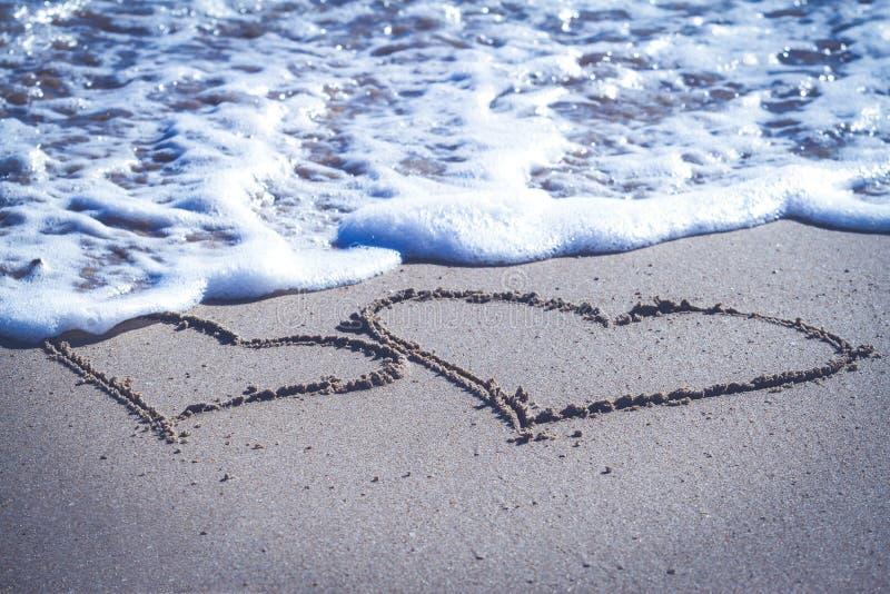 Zwei Herzen gezeichnet auf den Sand des Strandes und der blauen Meereswellen mit Schaum lizenzfreies stockfoto