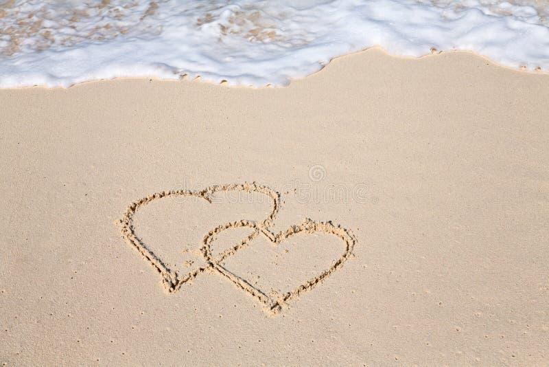 Zwei Herzen gezeichnet auf den Strandsand stockfotografie