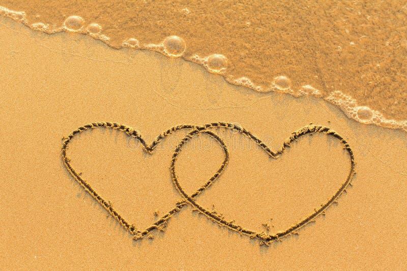 Zwei Herzen gezeichnet in den Meersand mit der weichen Welle Liebe stockbilder