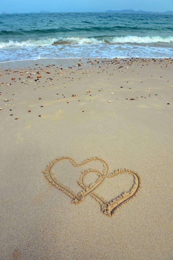 Zwei Herzen gezeichnet in Sand lizenzfreies stockfoto
