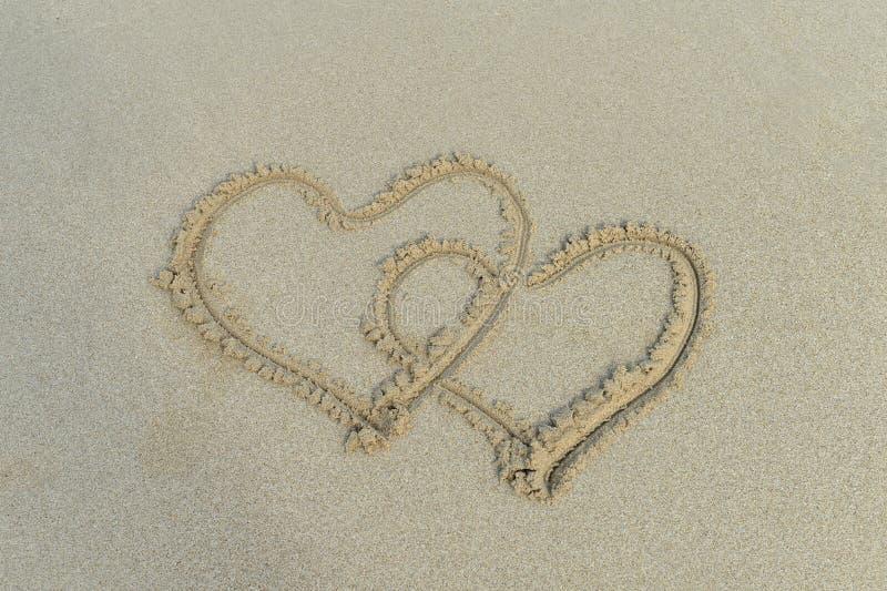 Zwei Herzen gezeichnet in Sand lizenzfreie stockfotografie