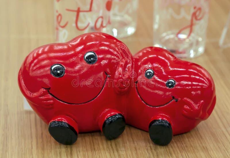 Zwei Herzen lächeln und Händchenhalten Keramische Figürchen von zwei Herzen stockbilder