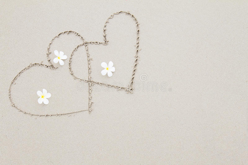 Zwei Herzen mit weißen Blumen auf dem Strandoberflächenhintergrund stockfoto