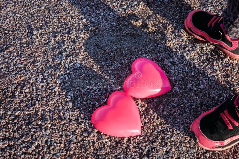 Zwei Herzen und das child& x27; s-Füße in den Turnschuhen auf Sand lizenzfreie stockfotos