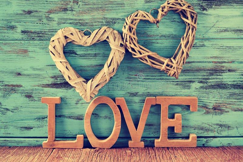 Zwei Herzen und hölzerne Buchstaben, die das Wort bilden, lieben lizenzfreie stockfotografie