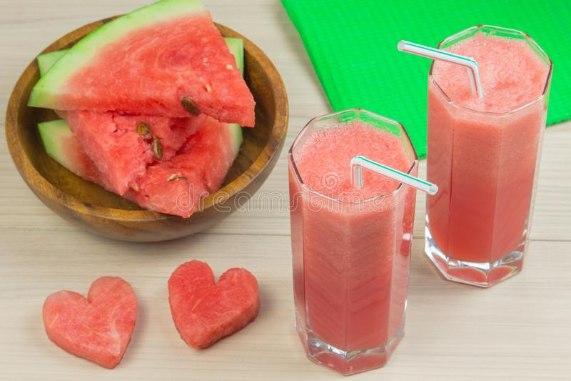 Zwei Herzen, Wassermelonensaft in zwei Glasgläsern mit einem Stroh auf einem hellen hölzernen Hintergrund, ein köstliches Cocktai lizenzfreies stockbild