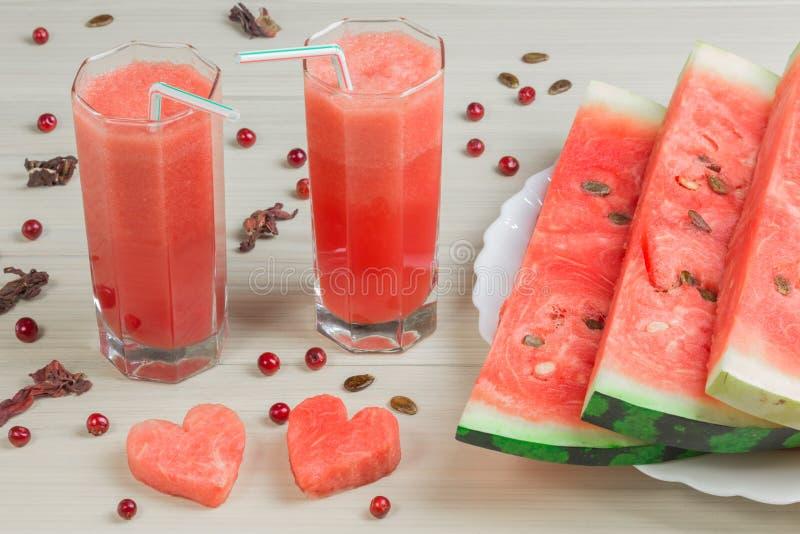 Zwei Herzen, Wassermelonensaft in zwei Glasschalen mit einem Stroh auf einem hellen hölzernen Hintergrund, ein köstliches Cocktai stockfotos