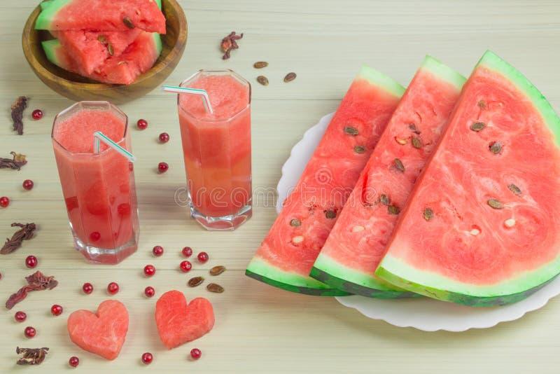 Zwei Herzen, Wassermelonensaft in zwei Glasschalen mit einem Stroh auf einem hellen hölzernen Hintergrund, ein köstliches Cocktai stockbild