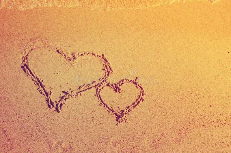 Zwei Herzen werden auf Sand gezeichnet lizenzfreie stockbilder