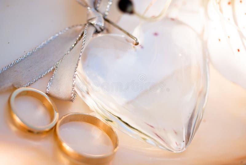 Zwei Hochzeitsringe ein Liebesinneres und eine Blume stockfoto