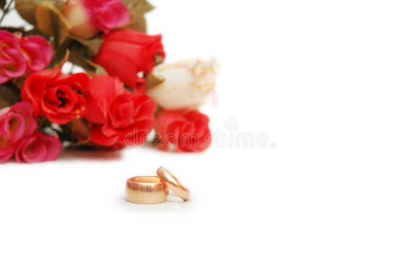 Zwei Hochzeitsringe und -blumen