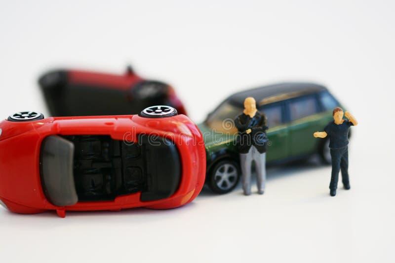 Zwei hoffnungslose Männer nahe den Spielzeugautos mit einbezogen in Unfall, in Begriffsbild in Miniaturen und in die Figürchen lo lizenzfreie stockfotografie