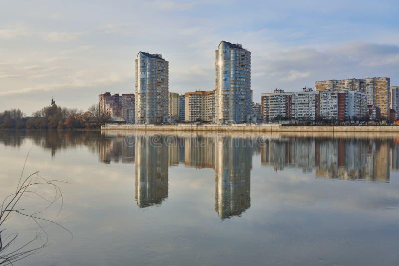 Zwei hohe Gebäude auf dem Hintergrund der alten Stadt von Krasnodar Anfang Dezember werden im Kuban-Fluss reflektiert lizenzfreie stockbilder