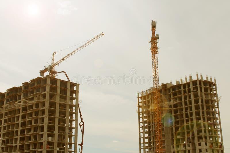 Zwei hohe Gebäude im Bau und zwei Kräne gegen den Himmel stockbild