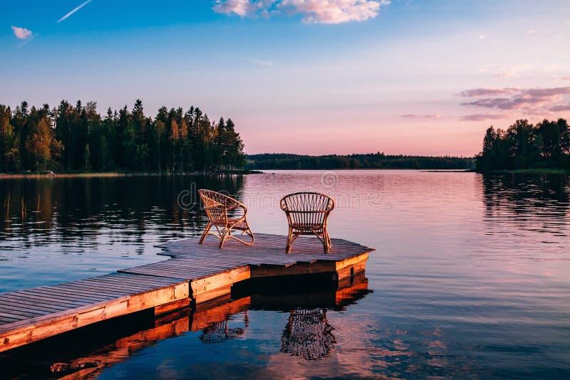 Zwei Holzstühle auf einem hölzernen Pier, der einen See bei Sonnenuntergang übersieht lizenzfreie stockfotos